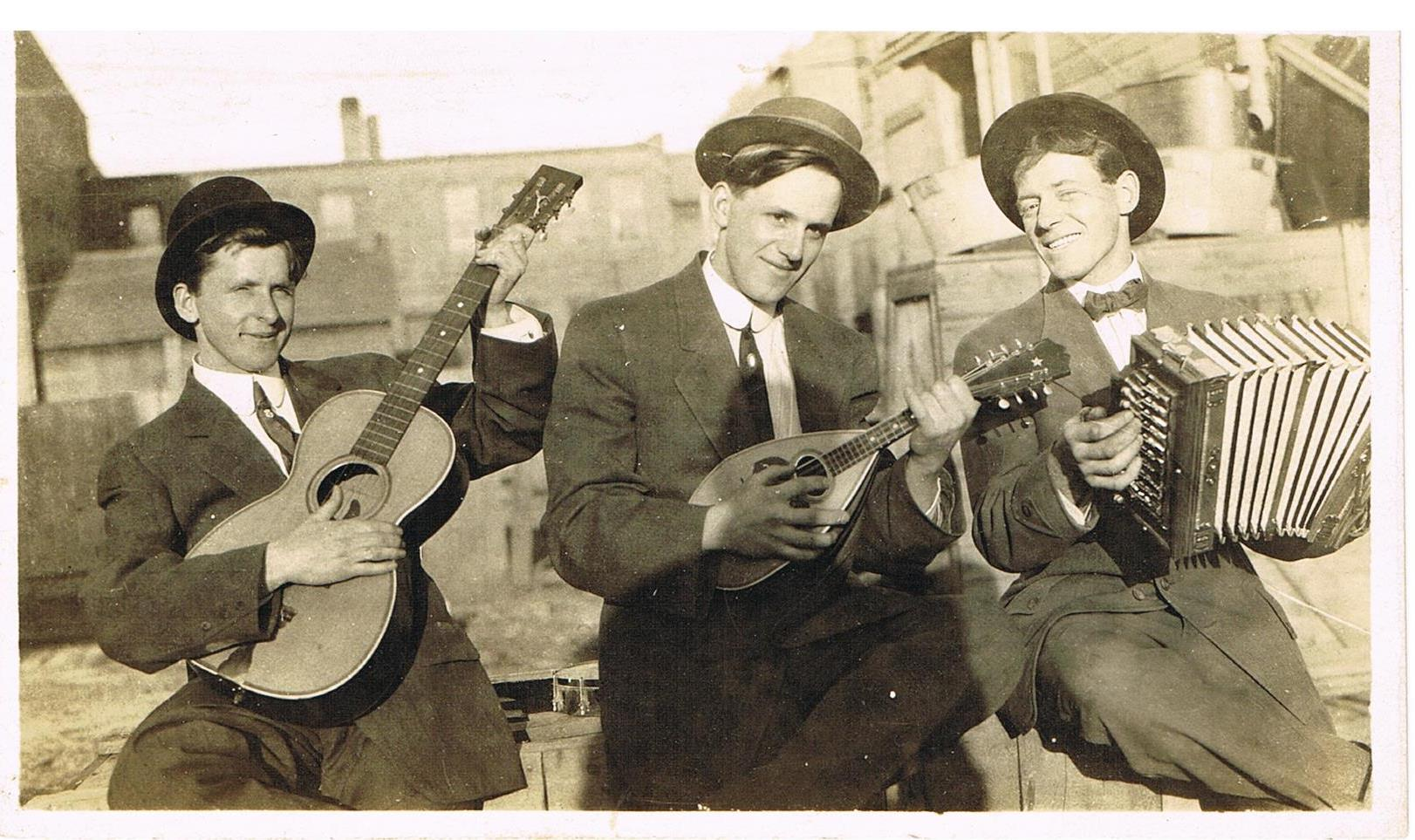 84.15.42 DBP259 PC Three musicians with hats and instruments guitar accordian c.1920